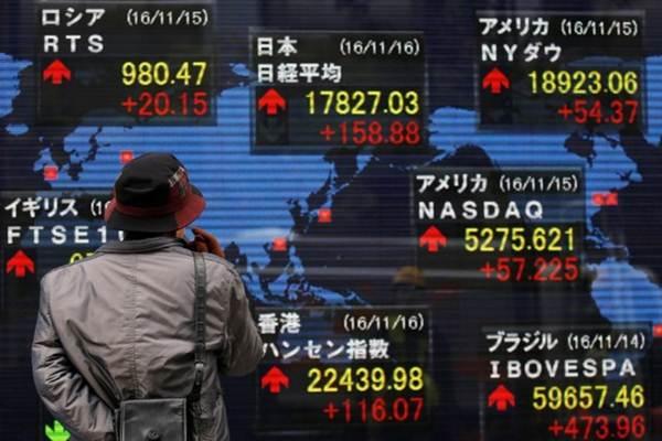 Seseorang sedanag melihat papan eletronik yang memperlihatkan indikasi saham di pasar modal Tokyo, Jepang. - Reuters