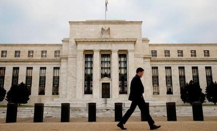 Seorang pria berjalan melewati Federal Reserve Bank di Washington, D.C., AS. - REUTERS / Kevin Lamarque