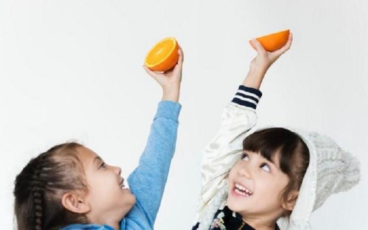 Ilustrasi: Kedua anak kecil yang senang saat mengonsumsi buah jeruk.