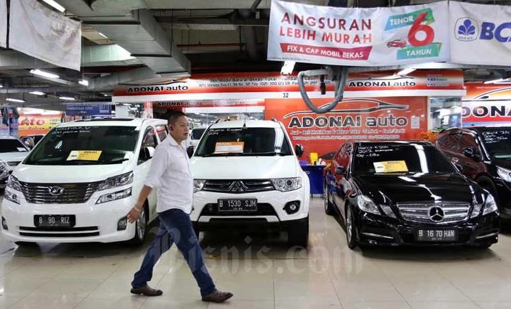 Pengunjung melintasi deretan mobil bekas yang dijual di Jakarta, Selasa (3/3/2020). Bisnis - Eusebio Chrysnamurti