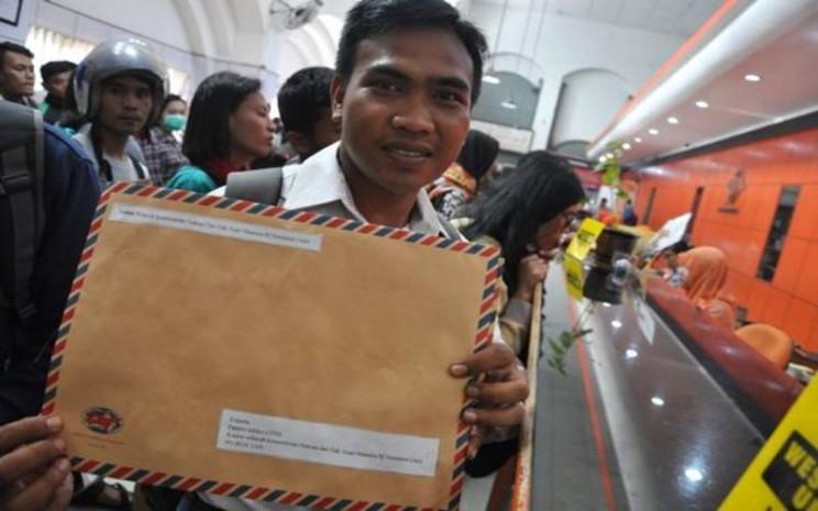 Seorang pelamar calon pegawai negeri sipil (CPNS) memperlihatkan berkas pendaftaran lamarannya untuk dikirim di Kantor Pos Besar Medan, Sumatera Utara, Senin (15/10). - Antara