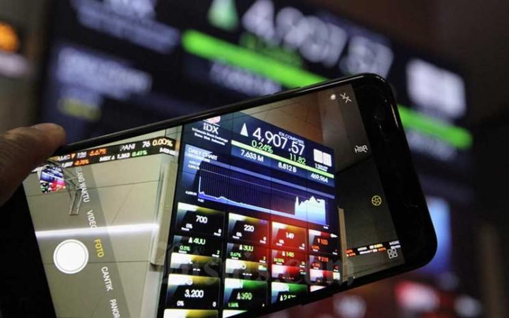 Pengunjung menggunakan ponsel saat berada didekat papan elektronik yang menampilkan perdagangan harga saham di lantai Bursa Efek Indonesia di Jakarta, Jumat (13/3/2020). Bisnis - Dedi Gunawan