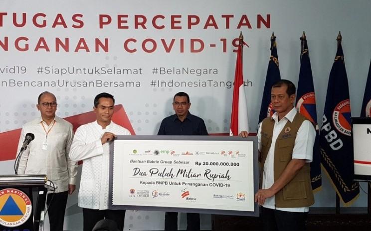 Pemimpin Bakrie Group Anindya Bakrie (Kedua dari Kiri) menyerahkan bantuan senilai Rp20 miliar kepada Ketua Gugus Tugas Percepatan Penanganan COVID-19 Doni Monardo (Kanan) di Graha BNPB, Jakarta, Jumat (27/3/2020) - Antara