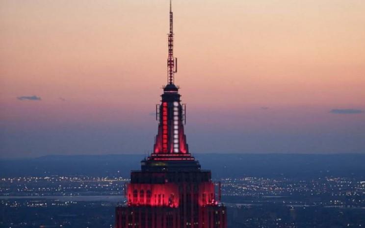Empire State Building memancarkan warna merah dan putih.