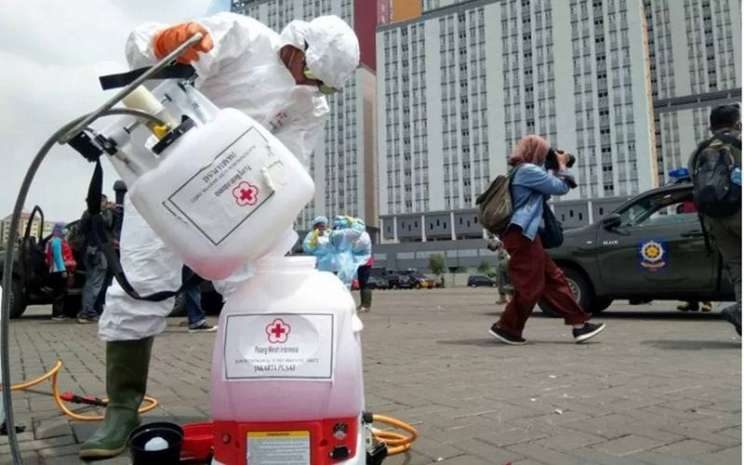 Petugas dari PMI Jakarta Pusat bersiap menyemprotkan disinfektan di dua menara Wisma Atlet Kemayoran, Jakarta, Sabtu (21/3/2020). - Antara