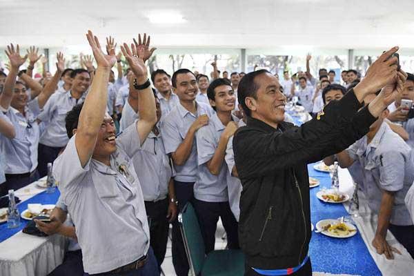 Presiden Joko Widodo (kanan) berswafoto dengan karyawan PT Yamaha Indonesia Motor Manufacturing di Jakarta, Senin (3/12/2018). Presiden menyempatkan waktu untuk makan siang bersama karyawan dan melepas pencapaian ekspor 1,5 juta unit sepeda motor Yamaha. - ANTARA/Puspa Perwitasari