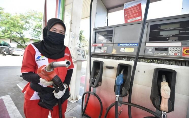Petugas SPBU Pertamina menggunakan masker dan sarunga tangan saat melayani konsumen. - Istimewa / Pertamina