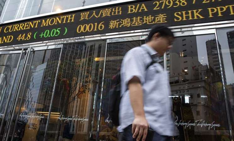 Seorang pejalan kaki berjalan melewati papan ticker elektronik yang menampilkan angka harga saham di luar kompleks Exchange Square di Hong Kong. -  Justin Chin / Bloomberg