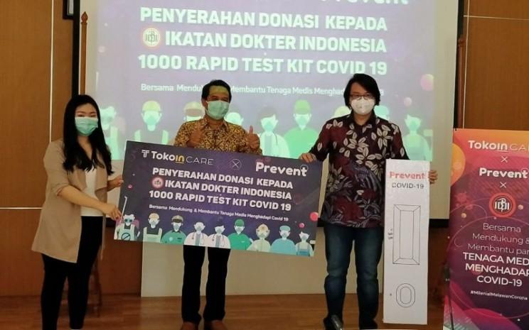 Ketua Umum IDI, dr. Daeng M. Faqih (tengah) menerima donasi 1.000 alat rapid test Covid-19 dari Tokoin yang diwakili Reiner B. Rahardja - CEO Tokoin Group (kanan) dan Prevent Homedik yang diwakili Gabriella Christy- Finance Director (kiri) - istimewa