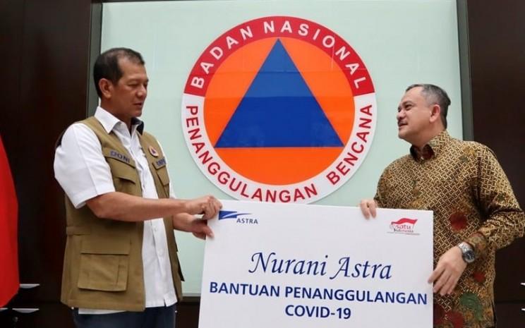 Kepala Badan Nasional Penanggulangan Bencana (BNPB) Doni Monardo (kiri) menerima bantuan secara simbolis dari Deputy Chief of Corporate Affairs Astra Riza Deliansyah (kanan) di Jakarta (30/3/2020) - Dokumen Astra