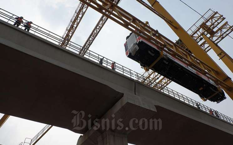 Rangkaian kereta (trainset) Light Rail Transit (LRT) Jakarta, Bogor, Depok, dan Bekasi (Jabodebek) diangkat ke lintasan Stasiun Harjamukti, Cibubur, Jakarta, Minggu (13/10). LRT Jabodetabek merupakan proyek yang digarap oleh PT Adhi Karya Tbk. Bisnis - Nurul Hidayat