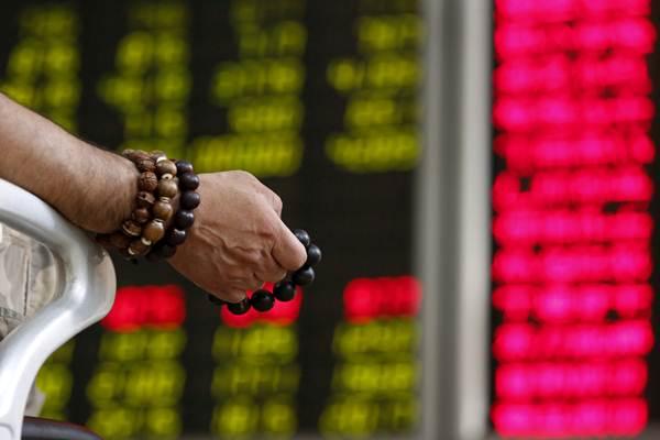 Seorang investor memegang manik-manik doa saat melihat papan yang menunjukkan harga saham di sebuah kantor broker di Beijing. - Reuters