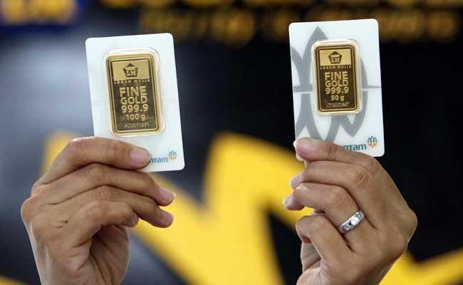 Karyawan menunjukan emas batangan di Butik emas Loga Mulia, Jakarta, Kamis (13/2/2020). Bisnis - Eusebio Chrysnamurti