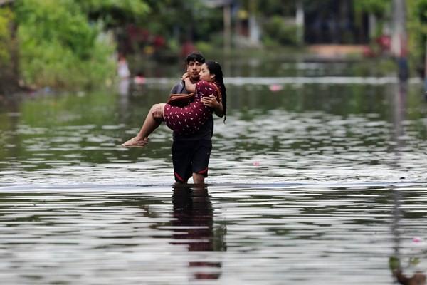 Seorang pria menggendong istrinya menembus genangan air. - Reuters/Henry Romero
