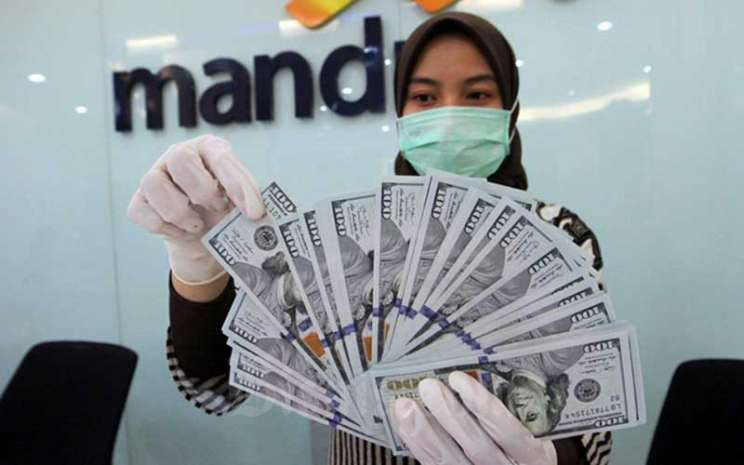 Karyawati bank menata uang dollar di kantor cabang PT Bank Mandiri Tbk. di Jakarta, Rabu (22/4/2020). Bisnis - Dedi Gunawan