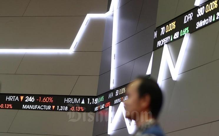 Karyawan melintasi layar monitor perdagangan Indeks Saham Gabungan (IHSG) di Bursa Efek Indonesia, Jakarta, Senin (17/2/2020). Bisnis - Eusebio Chrysnamurti