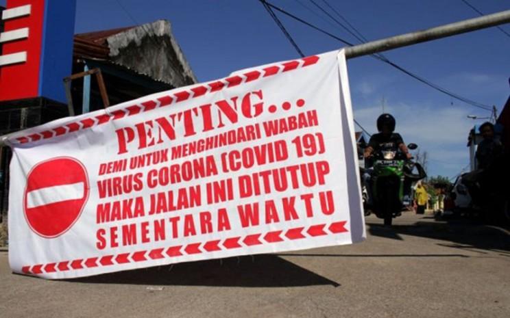 Salah satru jalan di Makassar ditutup untuk mencegah penyebaran corona./Antara - Arnas Padda
