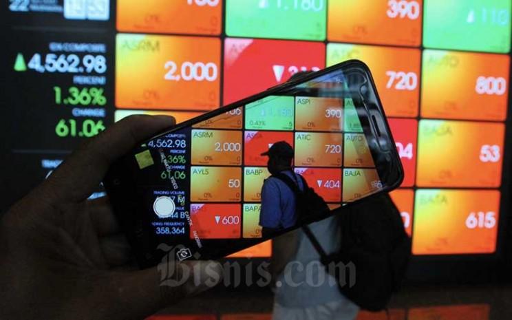 Pengunjung menggunakan smarphone didekat papan elektronik yang menampilkan perdagangan harga saham di Jakarta, Rabu (22/4/2020). Bisnis - Dedi Gunawan