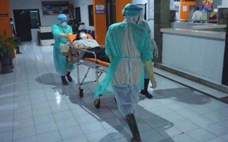 Ilustrasi-Petugas medis mengenakan alat pelindung diri mendorong ranjang beroda tempat pasien berstatus dalam pengawasan corona menuju ruang isolasi RSUD dr. Iskak di Tulungagung, Jawa Timur, pada Jumat (13/3/2020). - Antara