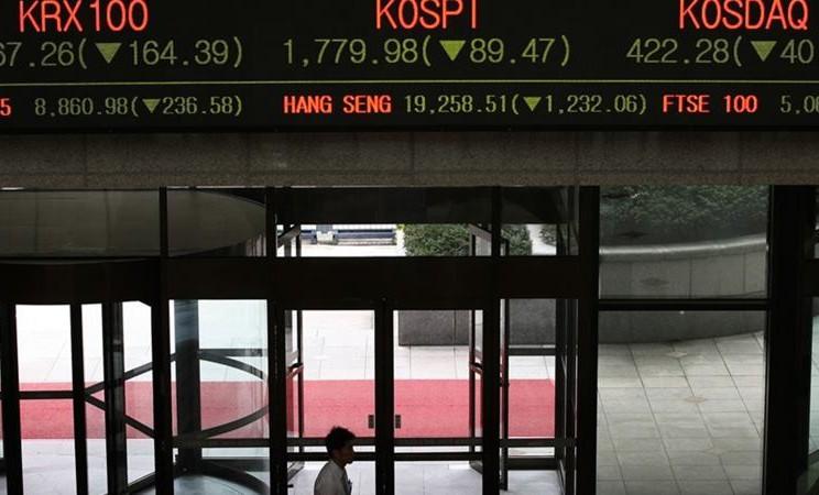 Seorang penjaga keamanan berjalan di bawah monitor di Bursa Efek Korea di Seoul. -  SeongJoon Cho / Bloomberg
