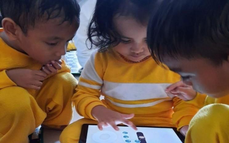 Anak sedang memegang gadget