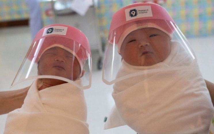 Dua bayi yang baru lahir menggunakan pelindung wajah di tengah pandemi virus corona COVID-19 di rumah sakit Praram 9, Bangkok, Thailand, Kamis (9/4/2020)./Antara - Reuters