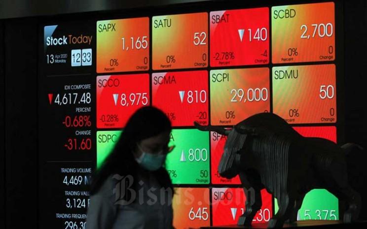 Pengunjung berjalan melintasi papan elektronik yang menampilkan perdagangan harga saham di Bursa Efek Indonesia, di Jakarta, Senin (13/4/2020). Bisnis - Dedi Gunawan