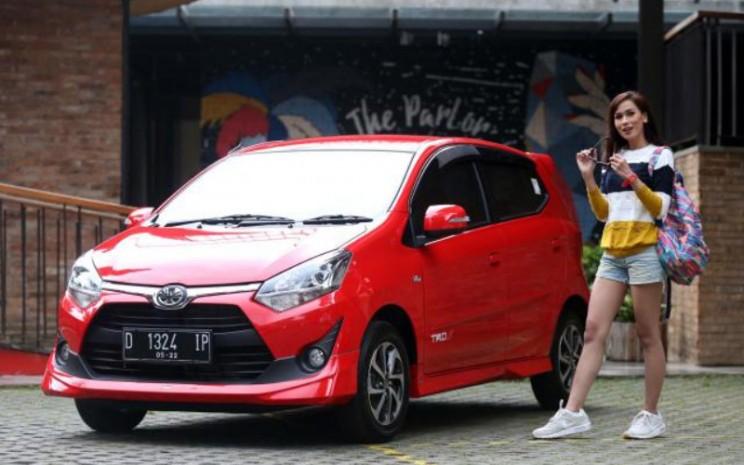 Model berpose di samping mobil Toyota New Agya di Bandung, Jawa Barat, Kamis (27/7/2019). Line-up terbaru segmen entry hatchback Toyota ini diharapkan memenuhi kebutuhan masyarakat Indonesia khususnya kawula muda.  - BISNIS.COM/RHN