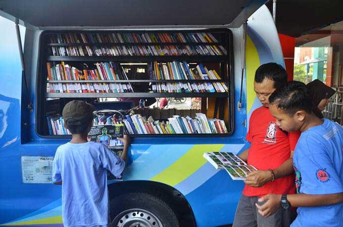 Warga membaca buku yang dipinjam dari mobil perpustakaan keliling di Alun-alun Kudus, Jawa Tengah, Minggu (10/2/2019). Perpustakaan keliling yang difasilitasi Perpustakaan Daerah (Perpusda) Kudus itu guna meningkatkan minat membaca masyarakat. - ANTARA/Yusuf Nugroho