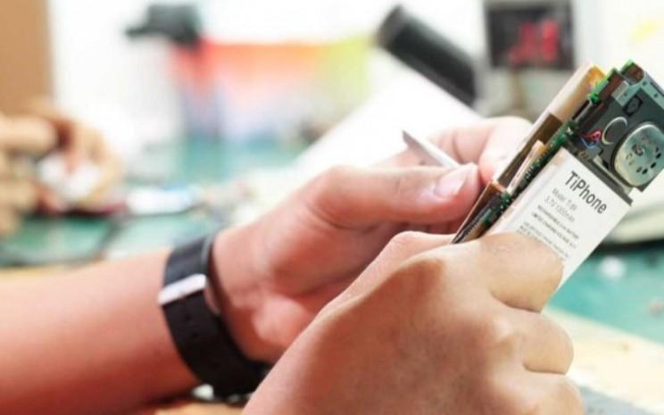 Seorang teknisi memperbaiki telepon selular. Service center merupakan salah satu lini usaha PT Tiphone Mobile Indonesia Tbk.  - tiphone.co.id