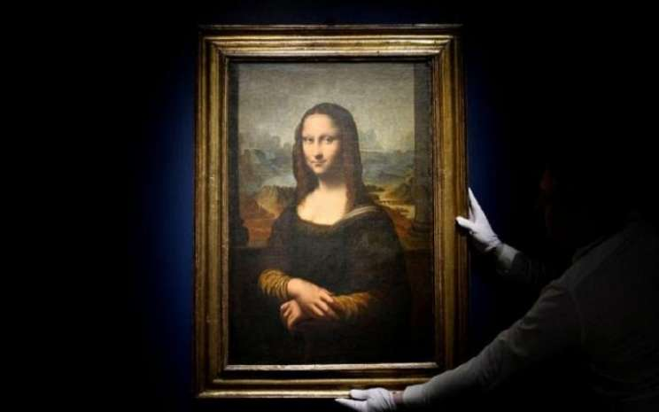 Seorang pekerja memasang salinan lukisan Mona Lisa abad ke-17 sebelum dilelang di rumah lelang Sotheby's di Paris, Prancis, 14 November 2019. - REUTERS/Johanna Geron