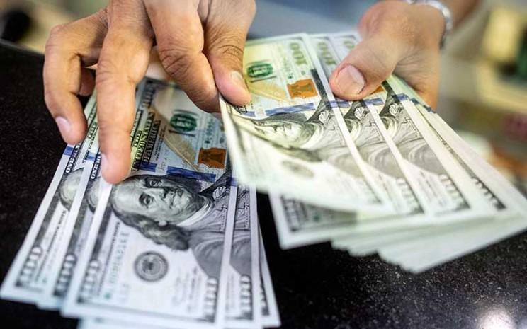 Karyawan menghitung uang dolar di gerai penukaran mata uang asing Ayu Masagung, Jakarta, Senin (18/5/2020). Nilai tukar rupiah terhadap dolar Amerika Serikat (AS) menguat pada penutupan perdagangan Senin (18/5) sebesar 10 poin atau 0,07 persen ke level Rp Rp14.850 per dolar AS. ANTARA FOTO - Aprillio Akbar