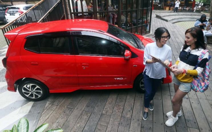 Staf pemasar menjelaskan spesifikasi mobil Toyota New Agya di Bandung, Jawa Barat, Kamis (27/7/2019). Line-up terbaru segmen entry hatchback Toyota ini diharapkan memenuhi kebutuhan masyarakat Indonesia khususnya kawula muda. - BISNIS.COM/Rachman