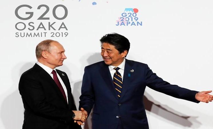 Presiden Rusia Vladimir Putin dan Perdana  Menteri Jepang Shinzo Abe bersalaman dalam KTT para pemimpin G20 di Osaka, Jepang, 28 Juni 2019. - Reuters