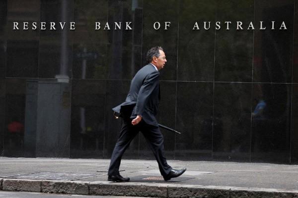 Seorang pebisnis melintasi kantor bank sentral Australia (Reserve Bank of Australia) di Sydney. - Reuters/Jason Reed