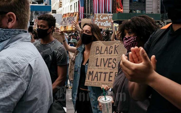 Warga menggelar demonstrasi mengecam rasisme dalam penegakan hukum dan pembunuhan George Floyd pada 25 Mei saat dalam tahanan Minneapolis saat rapat umum di Times Square di New York, Amerika Serikat, Senin (1/6/2020). Bloomberg/Getty Images - Scott Heins