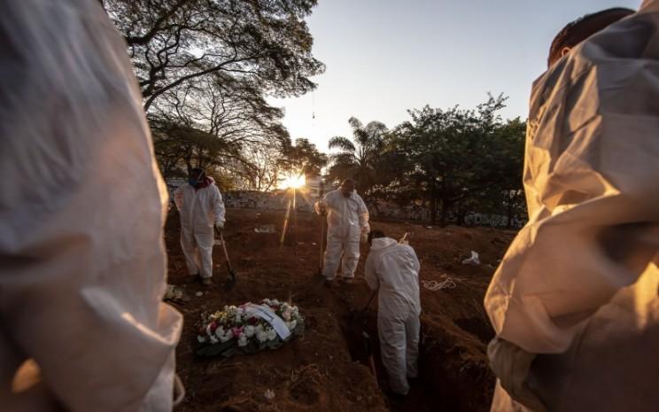 Petugas menguburkan korban virus corona di Brasil. (Bloomberg)
