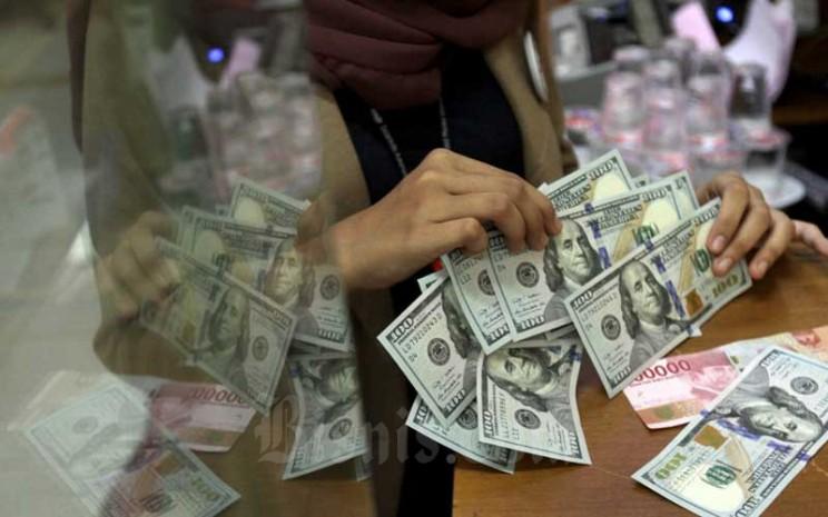 Karyawati menghitung uang Rupiah dan dolar AS di salah satu gerai penukaran mata uang asing di Jakarta, Minggu (7/6/2020). Bisnis - Arief Hermawan P