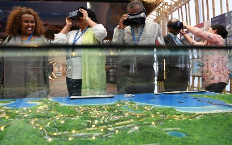 Sejumlah delegasi mencoba alat Virtual Reality (VR) dan Augmented Reality (AR) di Pavilion Indonesia pada pertemuan IMF World Bank Group 2018 di Nusa Dua, Bali. Pameran tersebut menampilkan pencapaian Indonesia mulai dari ekonomi, industri, infrastruktur hingga pariswisata. - Antara/Zabur Karuru.