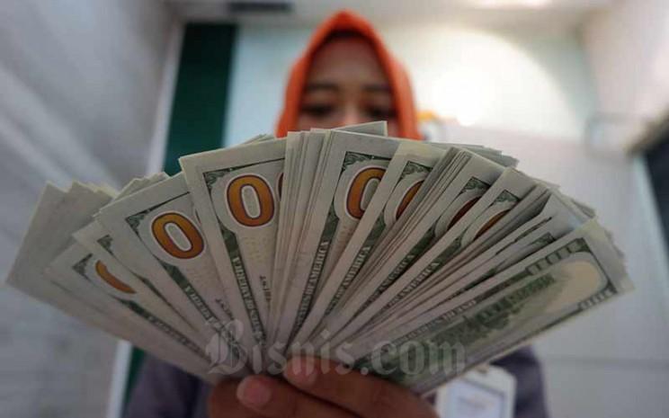 Karyawan menghitung uang dollar AS di salah satu tempat penukaran uang di Jakarta, Senin (11/3/2019). Bisnis - Nurul Hidayat