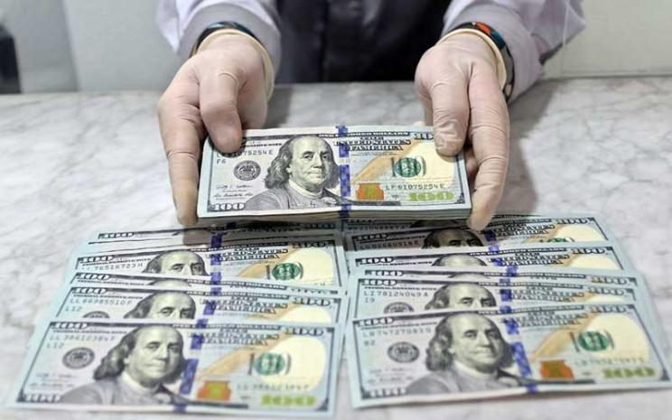 Karyawan menunjukan uang dolar Amerika Serikat (AS) di Jakarta, Rabu (17/6/2020). Bisnis - Eusebio Chrysnamurti