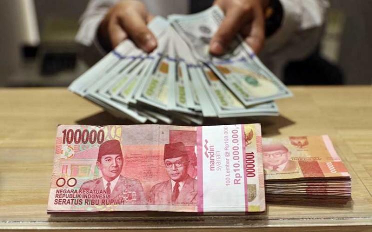 Karyawan menunjukan uang dolar Amerika Serikat (AS) di Jakarta, Senin (18/5/2020). Bisnis - Eusebio Chrysnamurti