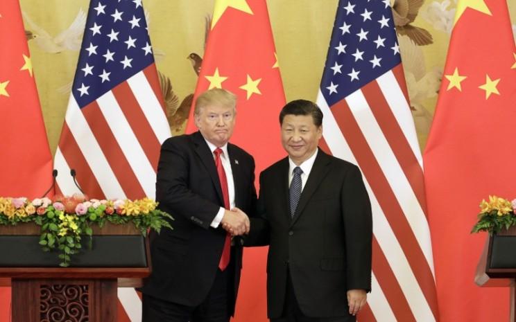 Presiden AS Donald Trump dan Presiden China Xi Jinping bersalaman dalam konferensi pers di Great Hall of the People di Beijing, China, Kamis (9/11/2017). - Bloomberg/Qilai Shen\\n