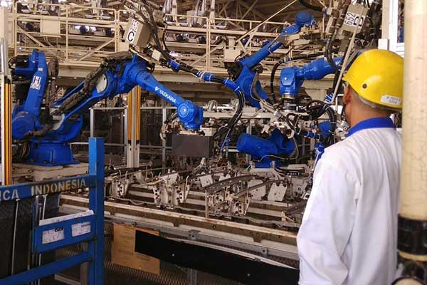Seorang pekerja mengawasi proses pengelasan atau welding yang dilakukan oleh robot di pabrik perakitan Suzuki Cikarang, Jawa Barat.  - Bisnis.com, Muhammad Khadafi