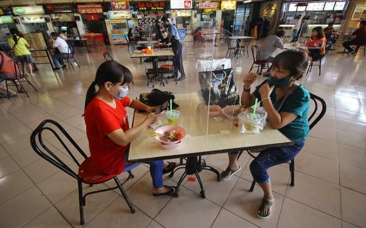 """Pengunjung menikmati makanan di meja makan yang bersekat di pusat jajanan serba ada (pujasera) atau """"food court"""" Pasar Atom, Surabaya, Jawa Timur, Selasa (9/6/2020). - Antara/Moch Asim\\n"""