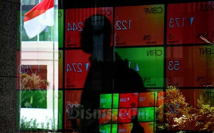 Pegawai melintas di depan layar monitor perdagangan Indeks Harga Saham Gabungan (IHSG) di Bursa Efek Indonesia di Jakarta, Rabu (3/6/2020). Bisnis - Abdurachman