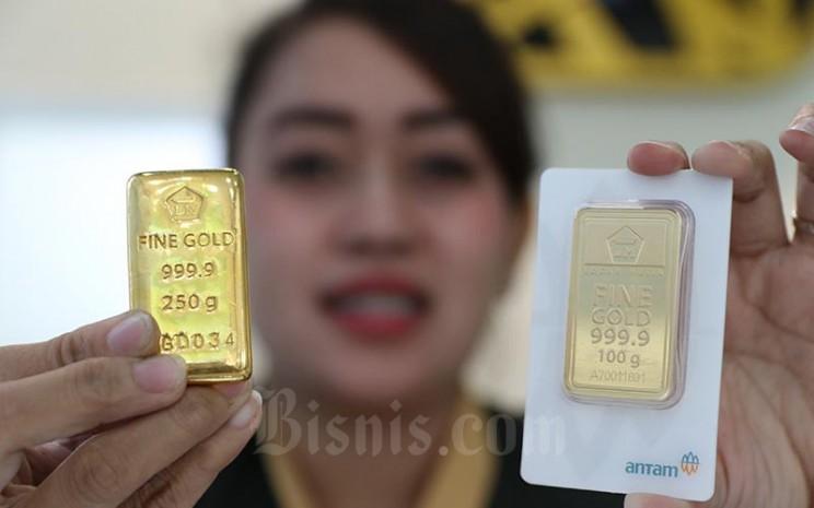 Karyawan menunjukan emas batangan di Butik Emas Logam Mulia, Jakarta, Kamis (13/2/2020). Bisnis - Eusebio Chrysnamurti