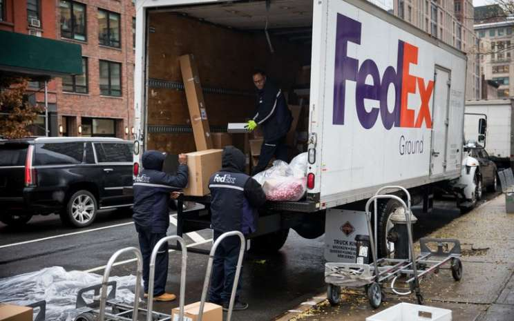 Pekerja FedEx melakukan bongkar muat barang di New York - Bloomberg / Michael Nagle