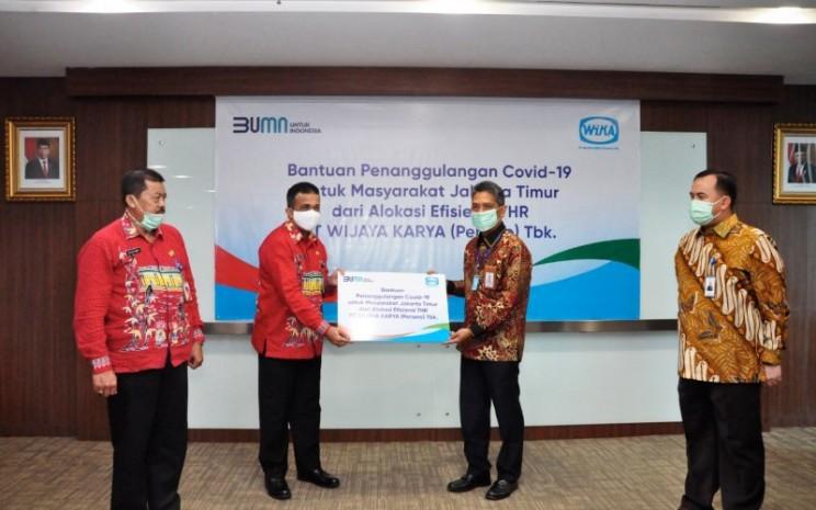 Direktur Utama WIKA, Agung Budi Waskito (kedua dari kanan) memberikan bantuan secara simbolis kepada Walikota Jakarta Timur M. Anwar, di Jakarta pada Kamis, (2/7). - WIKA