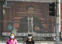 Warga berjalan di depan layar monitor yang menampilkan Presiden China Xi Jinping dalam National People\\\'s Congress di Beijing, China, Jumat (22/5/2020)./Bloomberg-Qilai Shen\\n